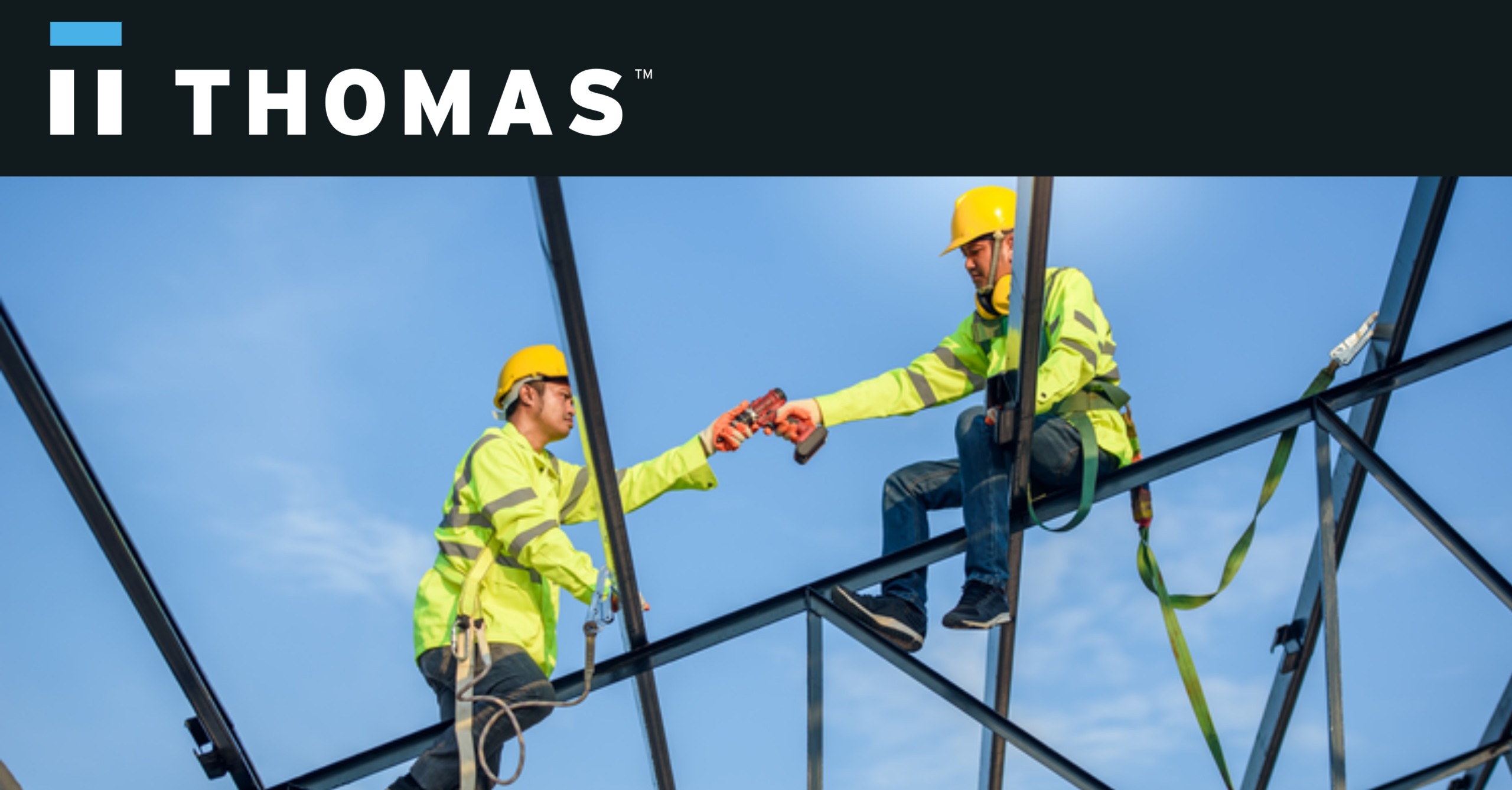 Two men sitting on a construction site, the one is handing a tool to the other.